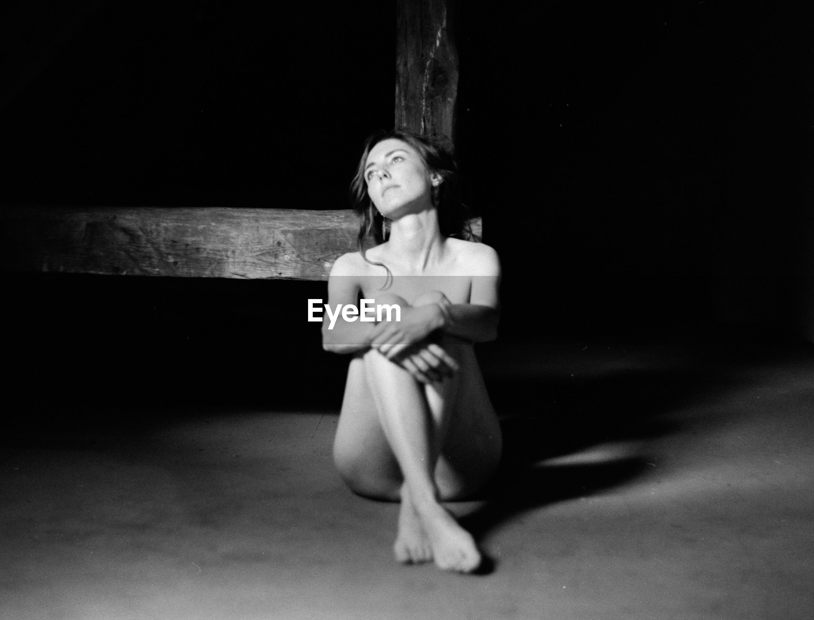 Sad naked woman sitting in darkroom