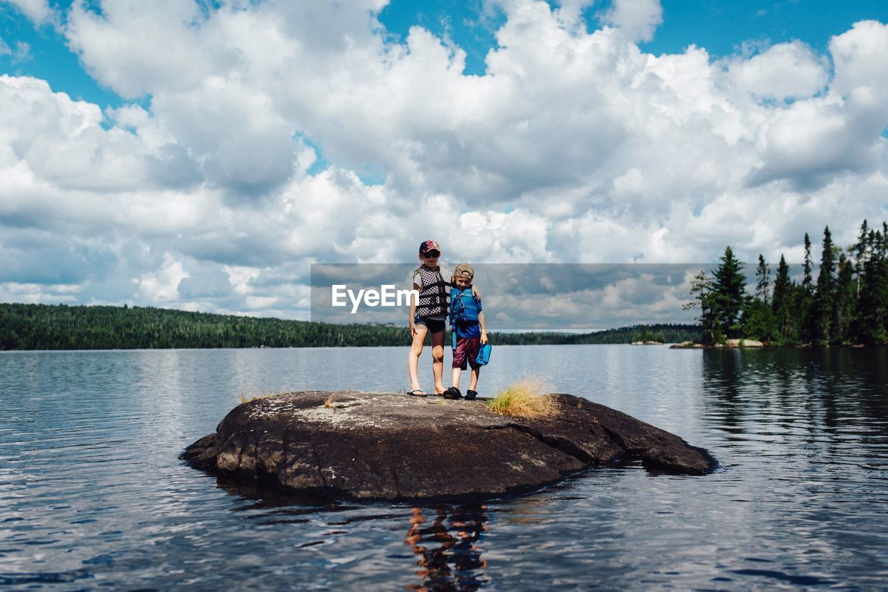 Low Angle View Of Boys Standing On Rock In Lake