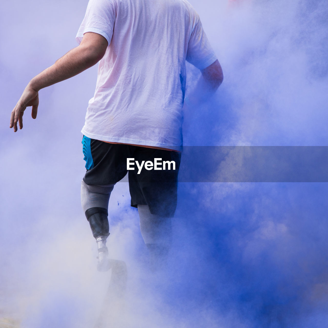 Low Section Of Disabled Person Walking In Blue Powder Paint
