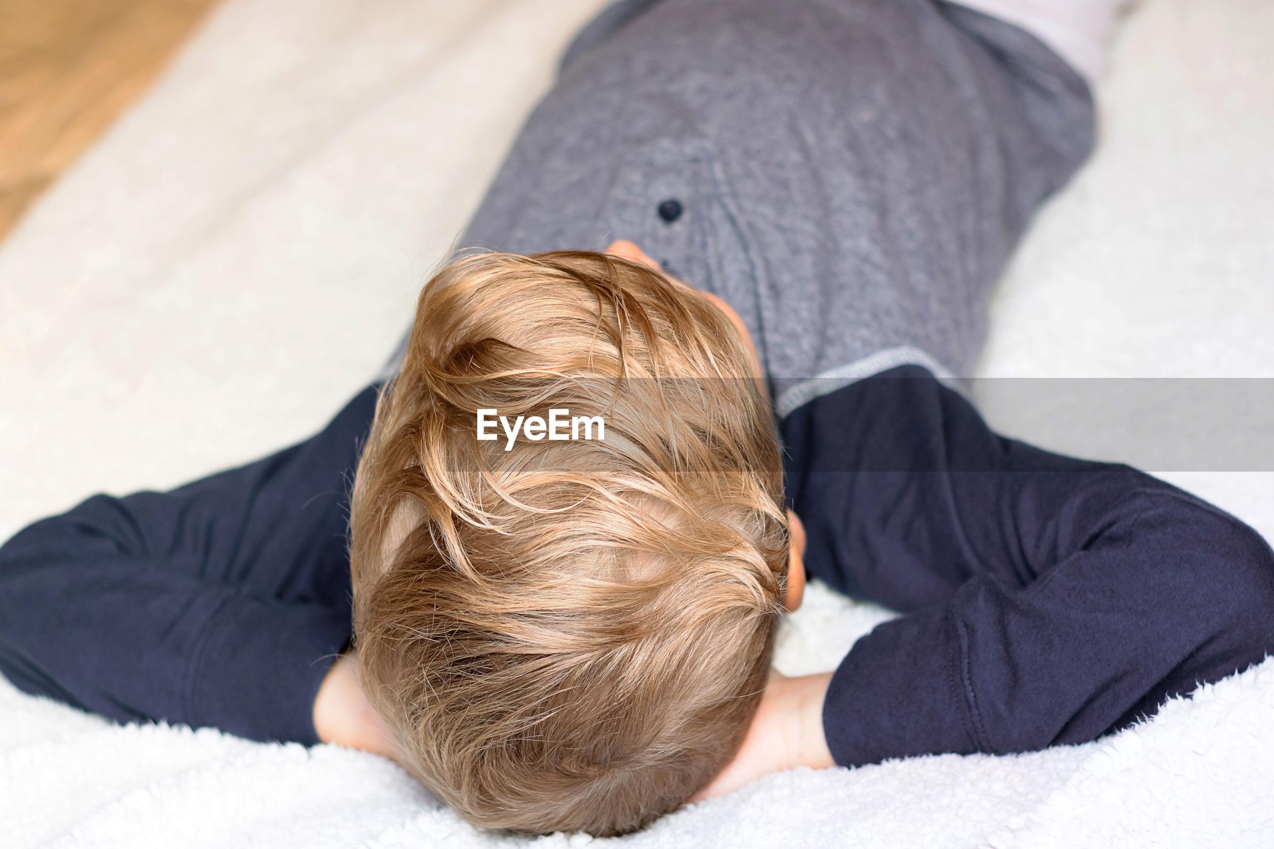 REAR VIEW OF BOY LYING ON BLANKET