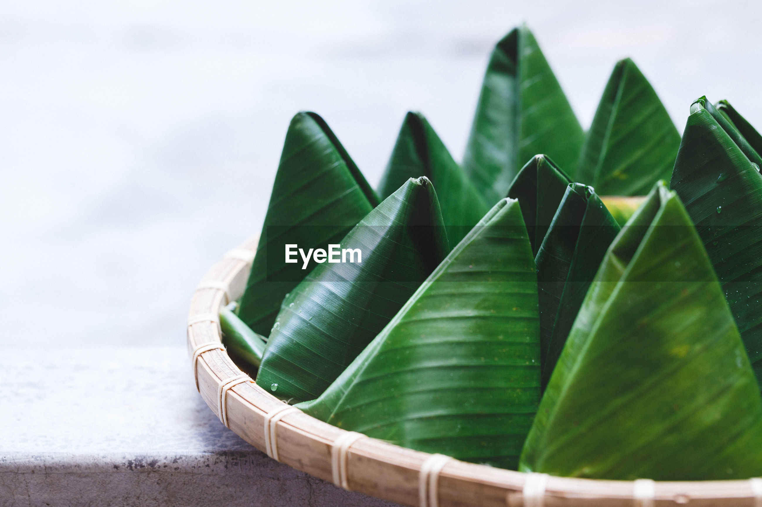 Close-up of sweet food wrapped in banana leaves in containers at table