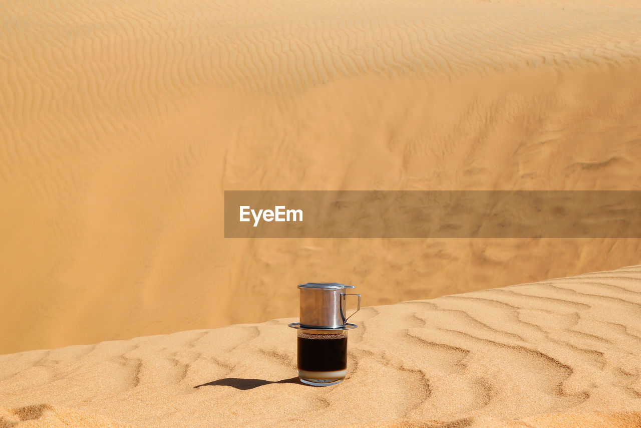 land, sand, sand dune, desert, beach, container, no people, nature, brown, indoors, still life, arid climate, tranquility, day, bottle, climate, sunlight, absence, beige, food and drink