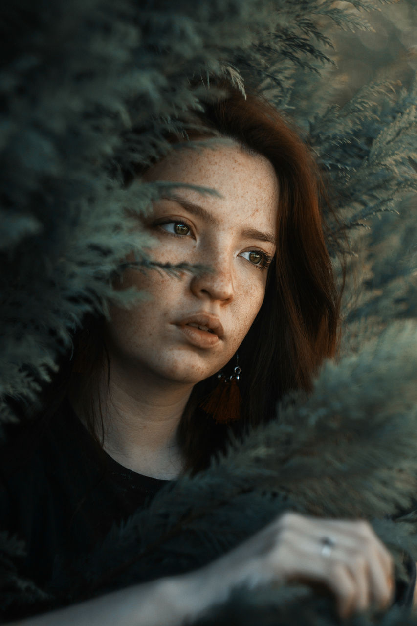 Close-up of thoughtful young woman amidst plants