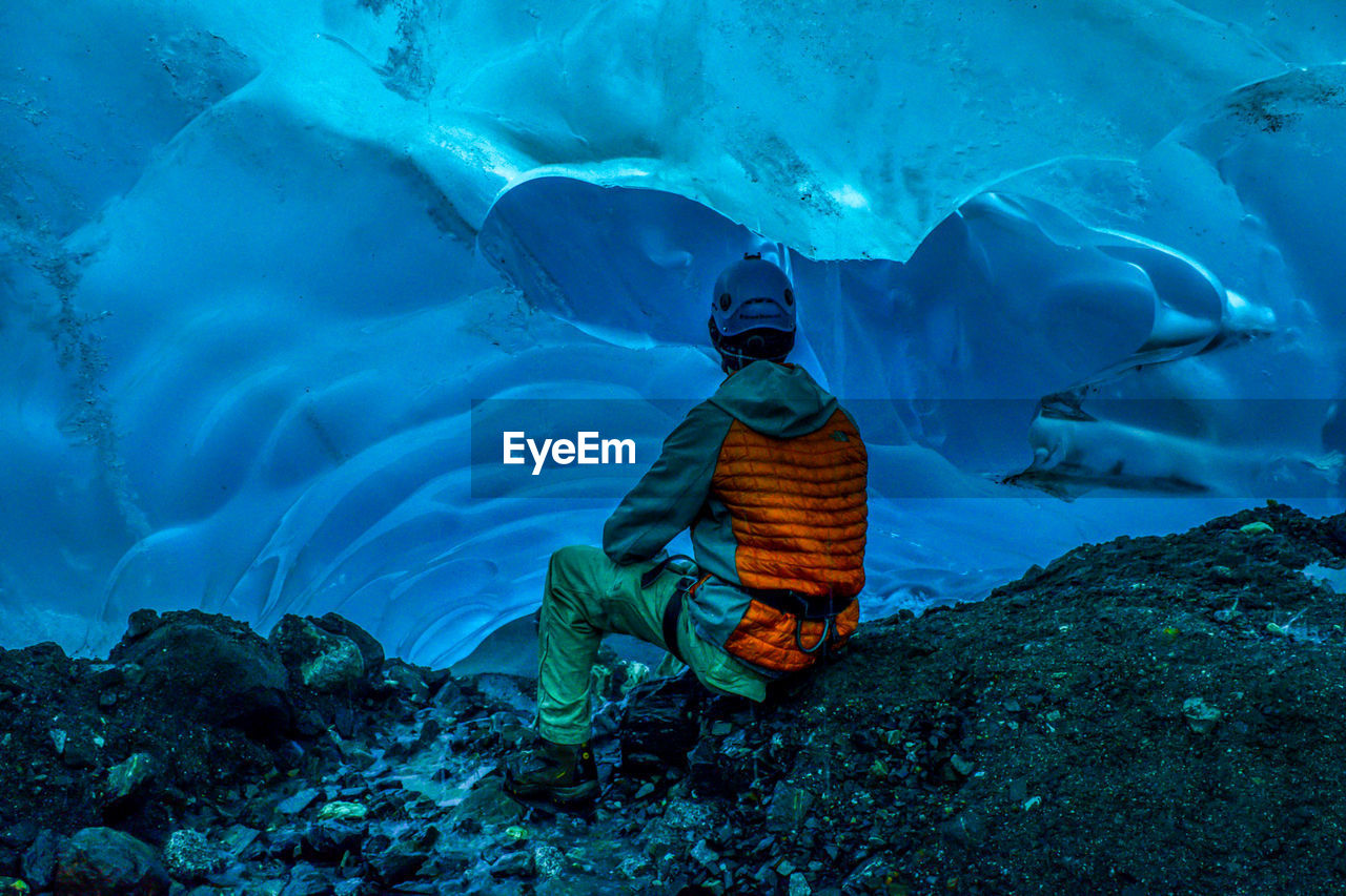 Rear View Of Man Sitting In Frozen Cave