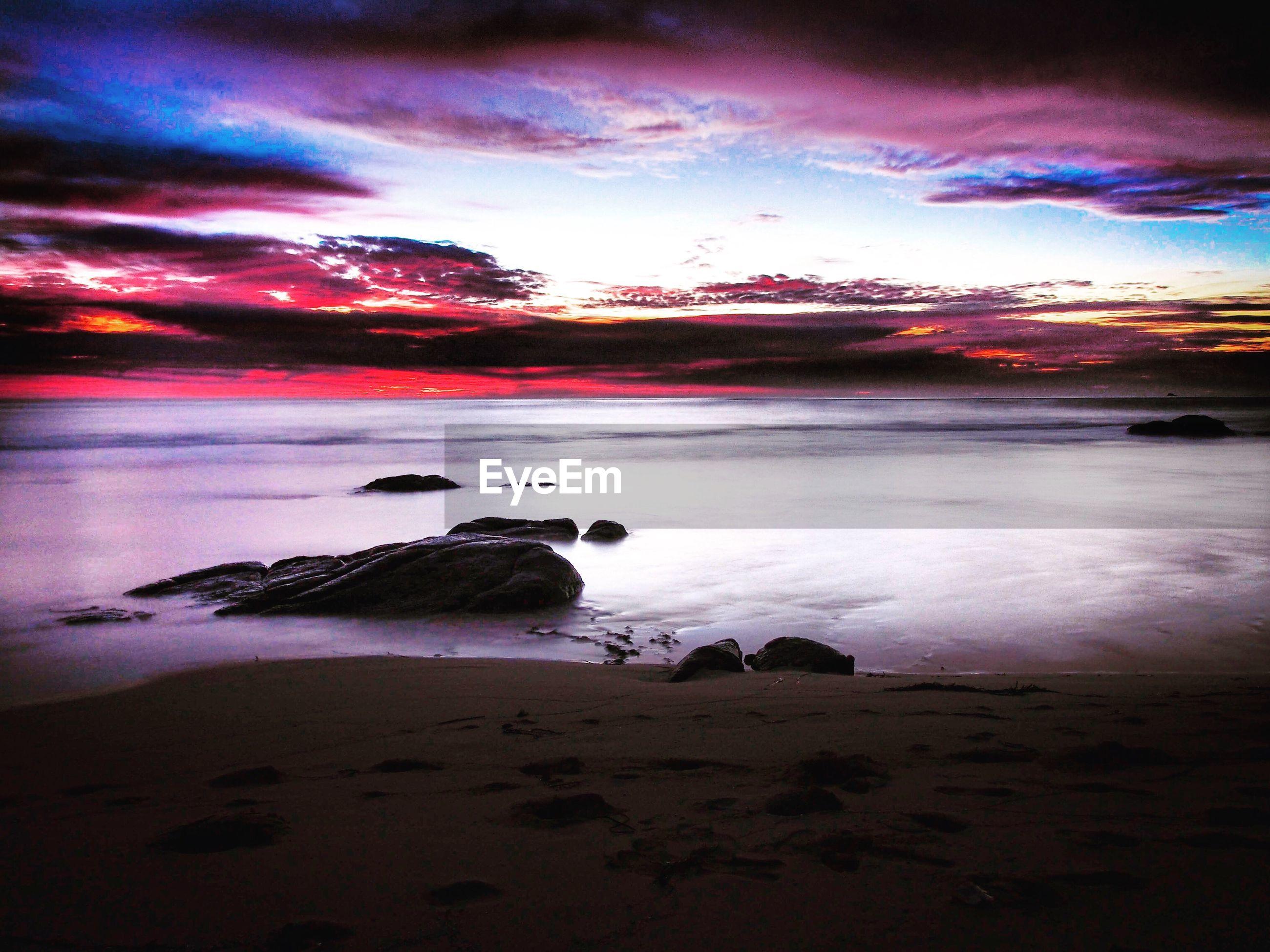 water, sky, beach, sunset, sea, scenics, tranquil scene, shore, cloud - sky, beauty in nature, tranquility, nature, dusk, cloudy, idyllic, rock - object, coastline, sand, cloud, dramatic sky