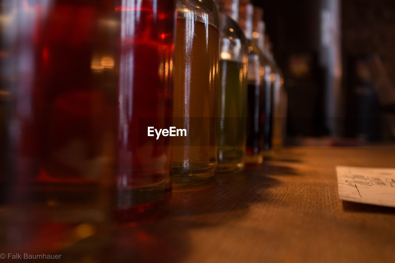 Close-up of alcohol bottles in row on table