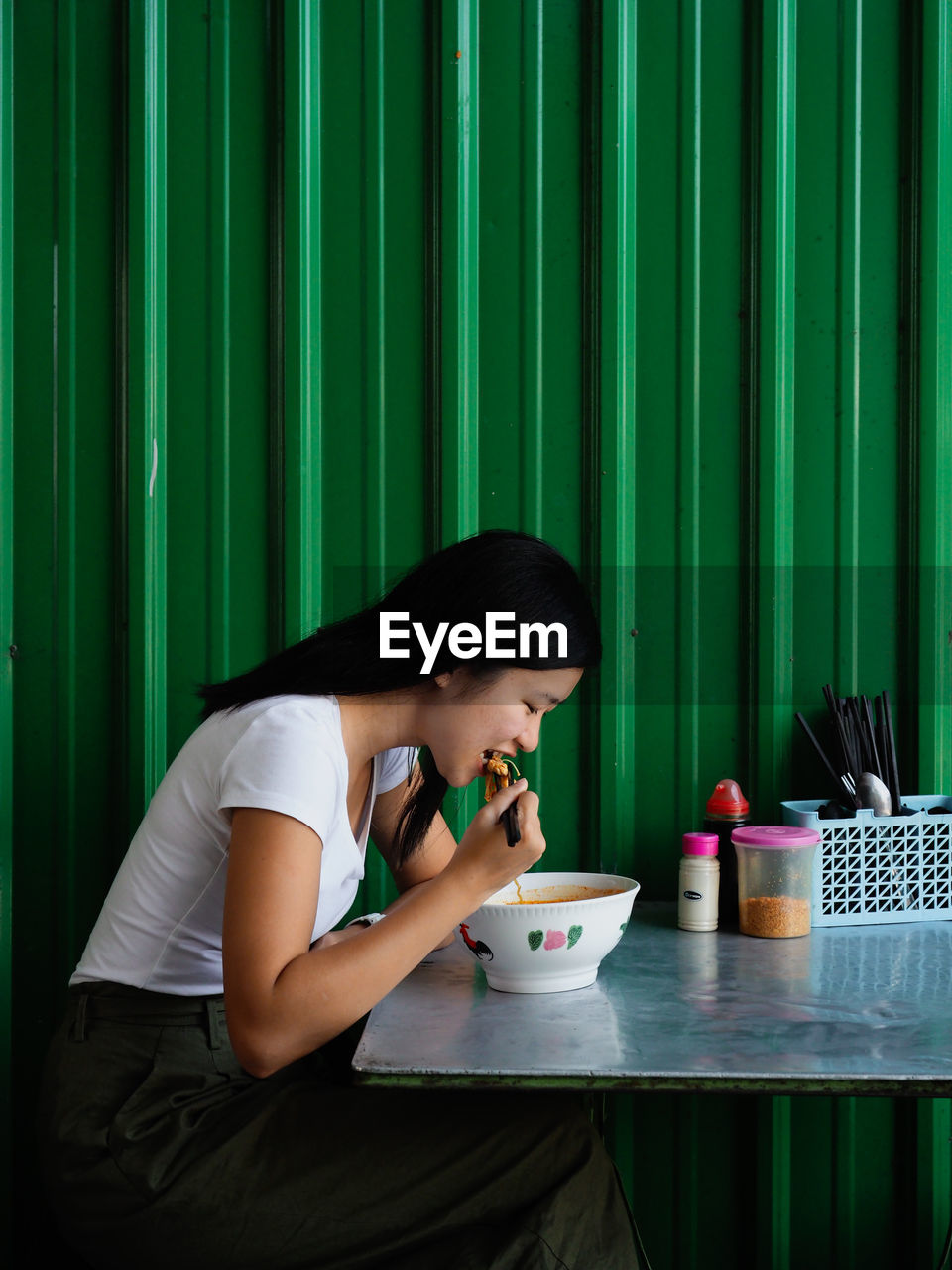 Side view of woman eating food while sitting at table