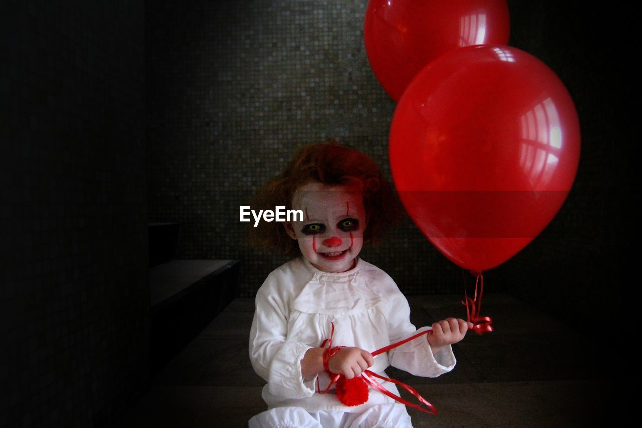 Girl in spooky costume holding red balloons