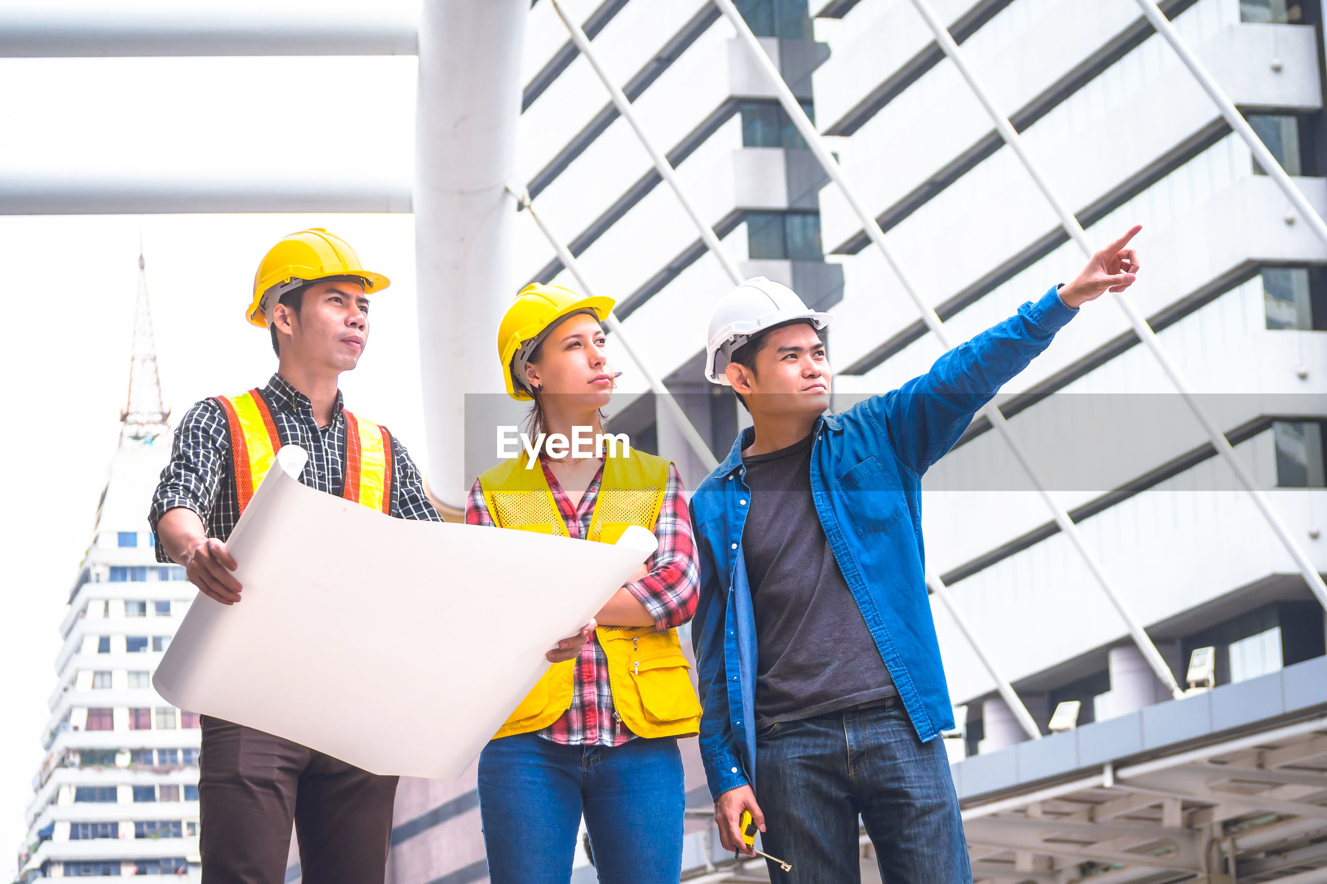 Three engineers discussing over blueprint while standing outdoors