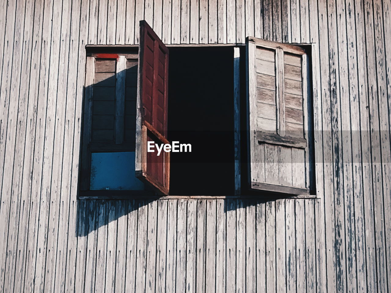 Low Angle View Of Wooden House With Open Window During Sunny Day