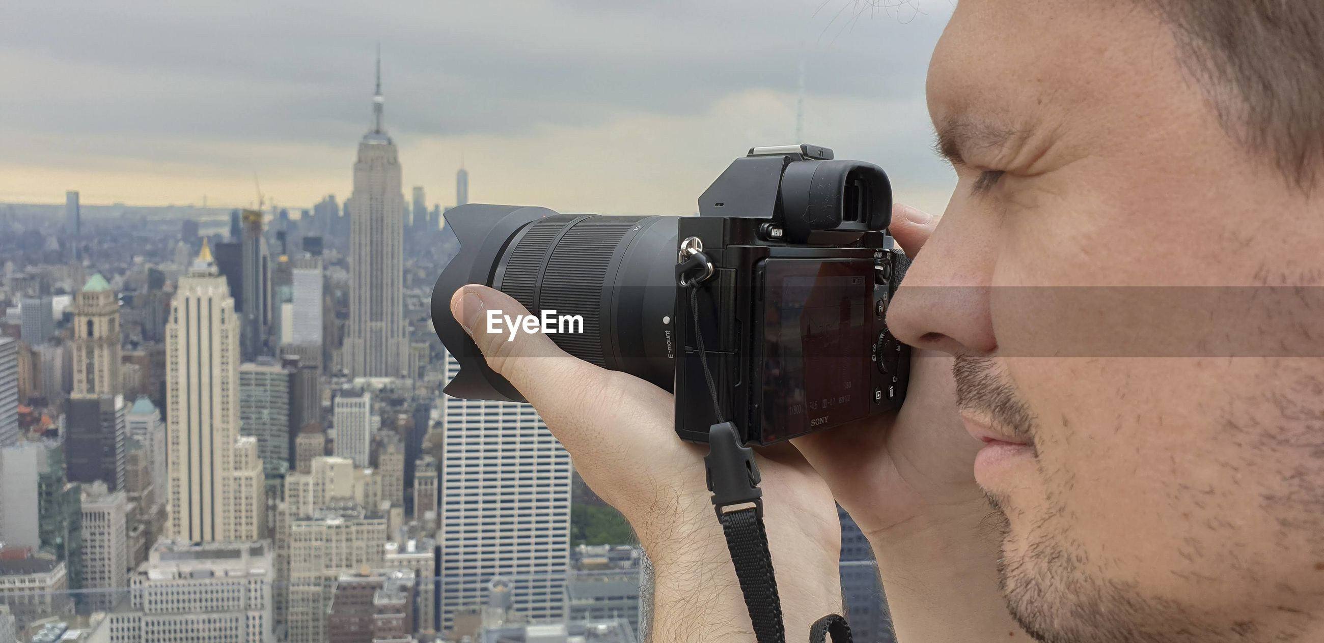 Man photographing cityscape against sky