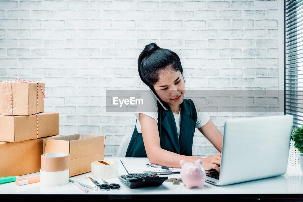 computer, one person, wireless technology, technology, laptop, business person, indoors, table, businesswoman, using laptop, working, business, communication, brick wall, women, adult, concentration, office, black hair, brick, hair, hairstyle