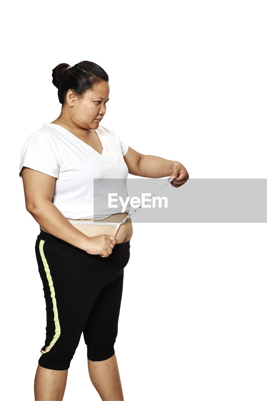 Fat woman measuring belly against white background