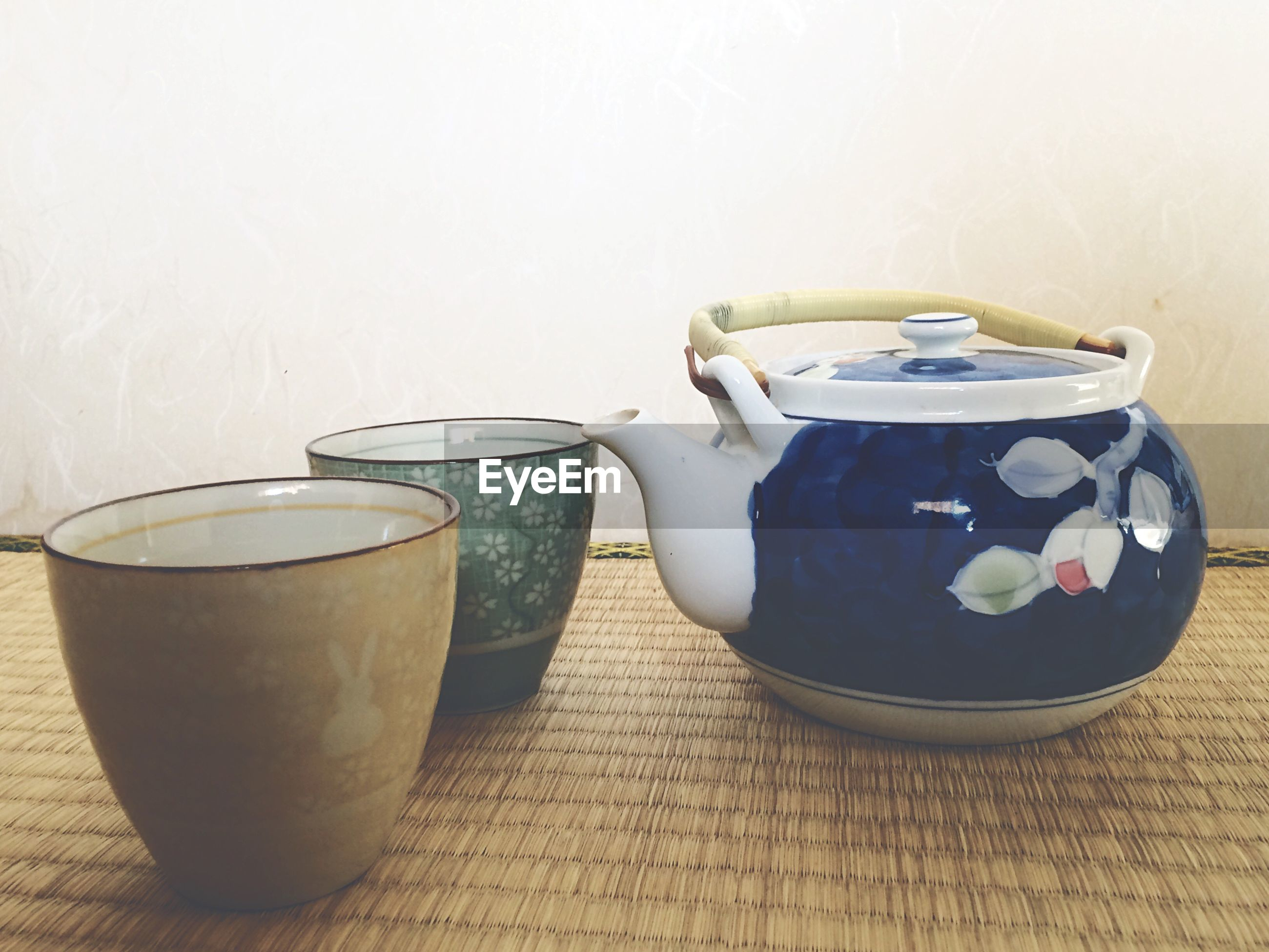 Close-up of cups with teapot on table