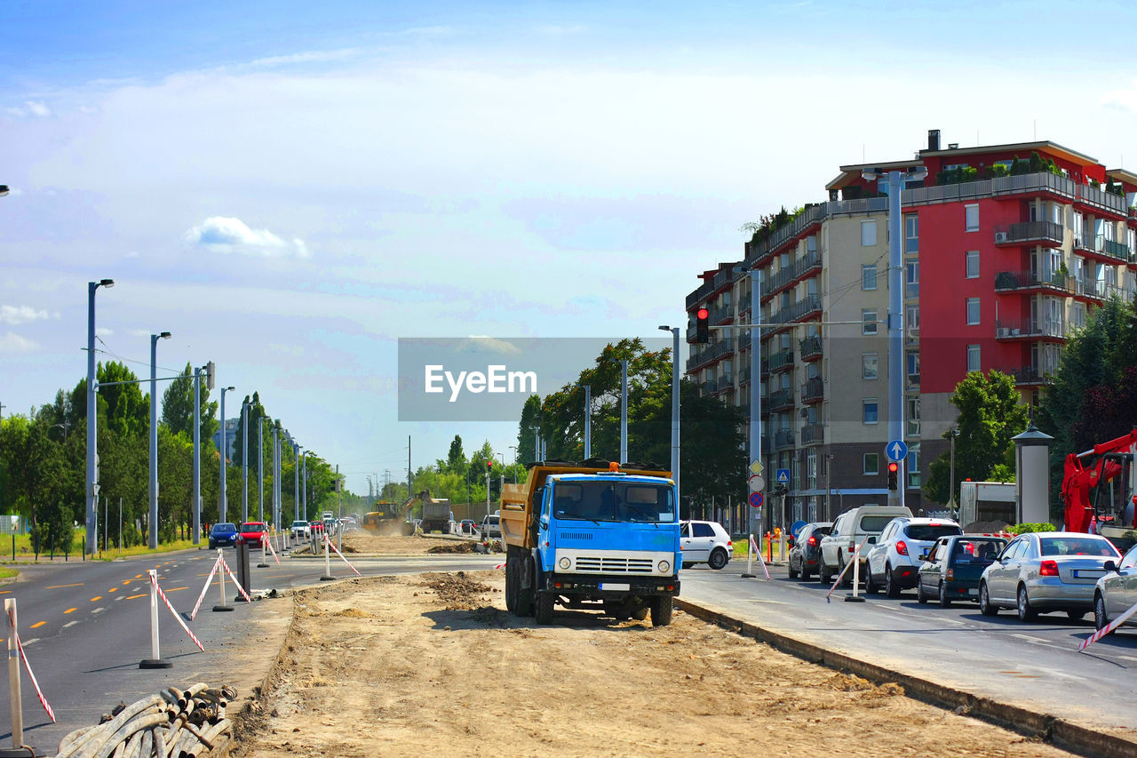 Road construction by buildings in city against sky