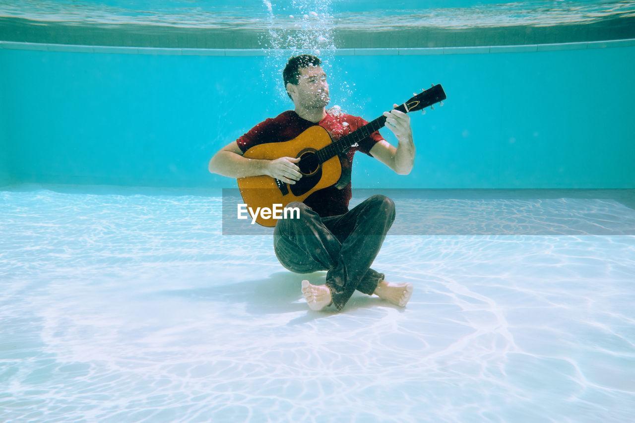 Man playing guitar underwater