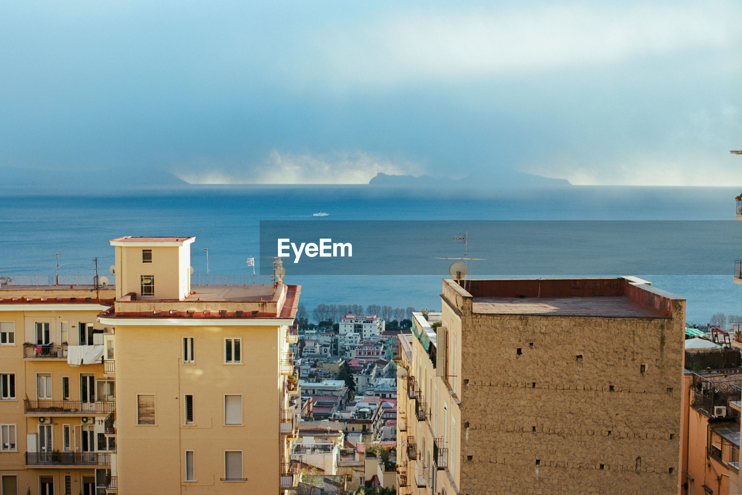 HIGH ANGLE VIEW OF BUILDINGS AGAINST SEA