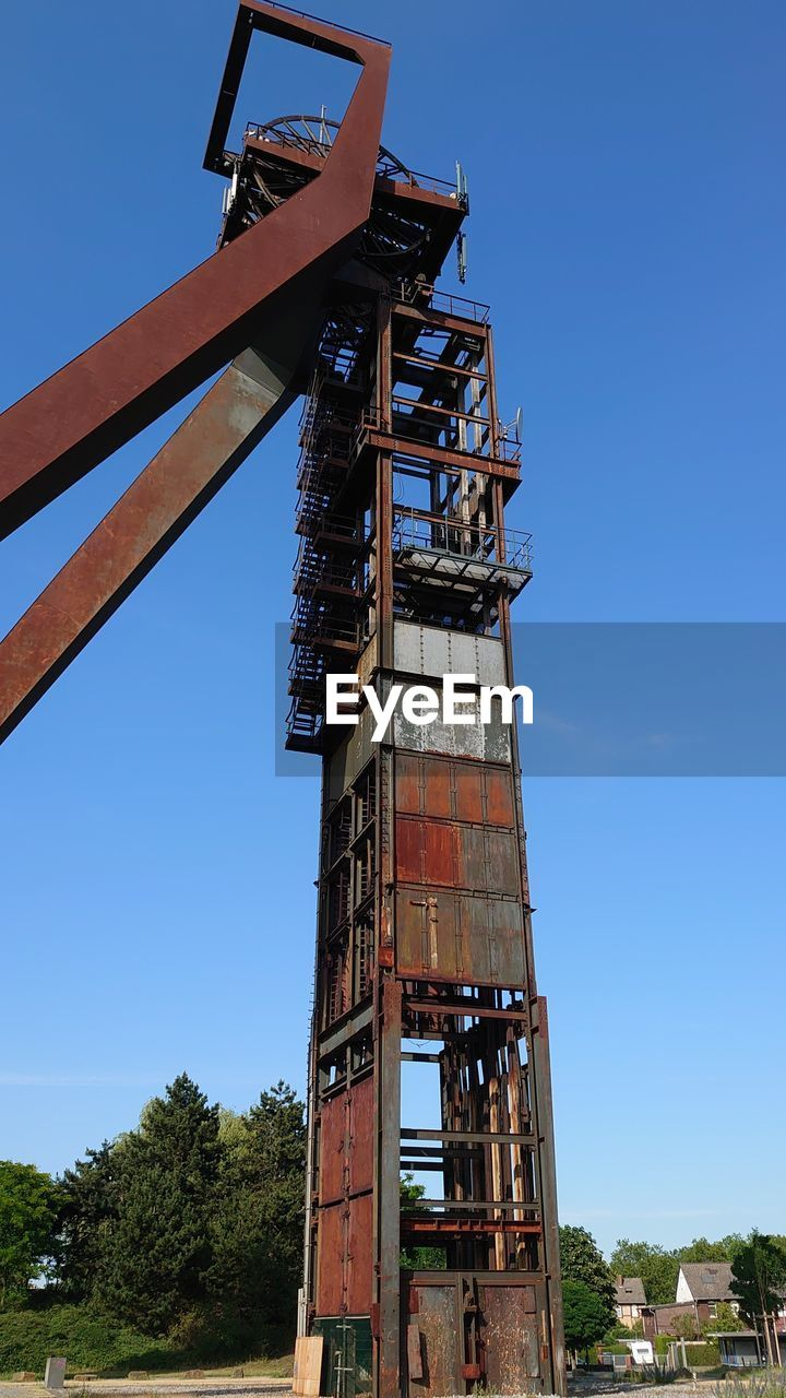 sky, architecture, clear sky, built structure, nature, tree, low angle view, blue, day, no people, plant, industry, building exterior, metal, machinery, tower, outdoors, tall - high, old, fuel and power generation, industrial equipment
