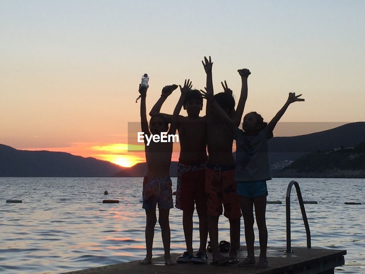 sky, water, sunset, real people, group of people, men, leisure activity, arms raised, friendship, human arm, lifestyles, standing, nature, togetherness, sea, adult, people, beauty in nature, outdoors, positive emotion
