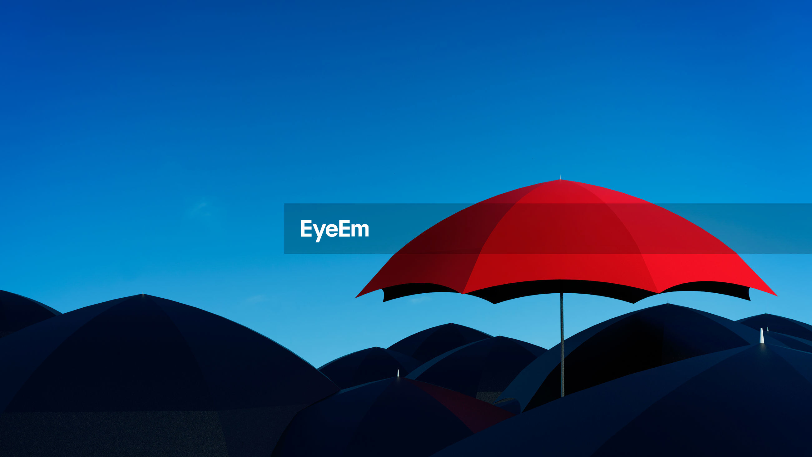 Red umbrella against clear blue sky during dusk
