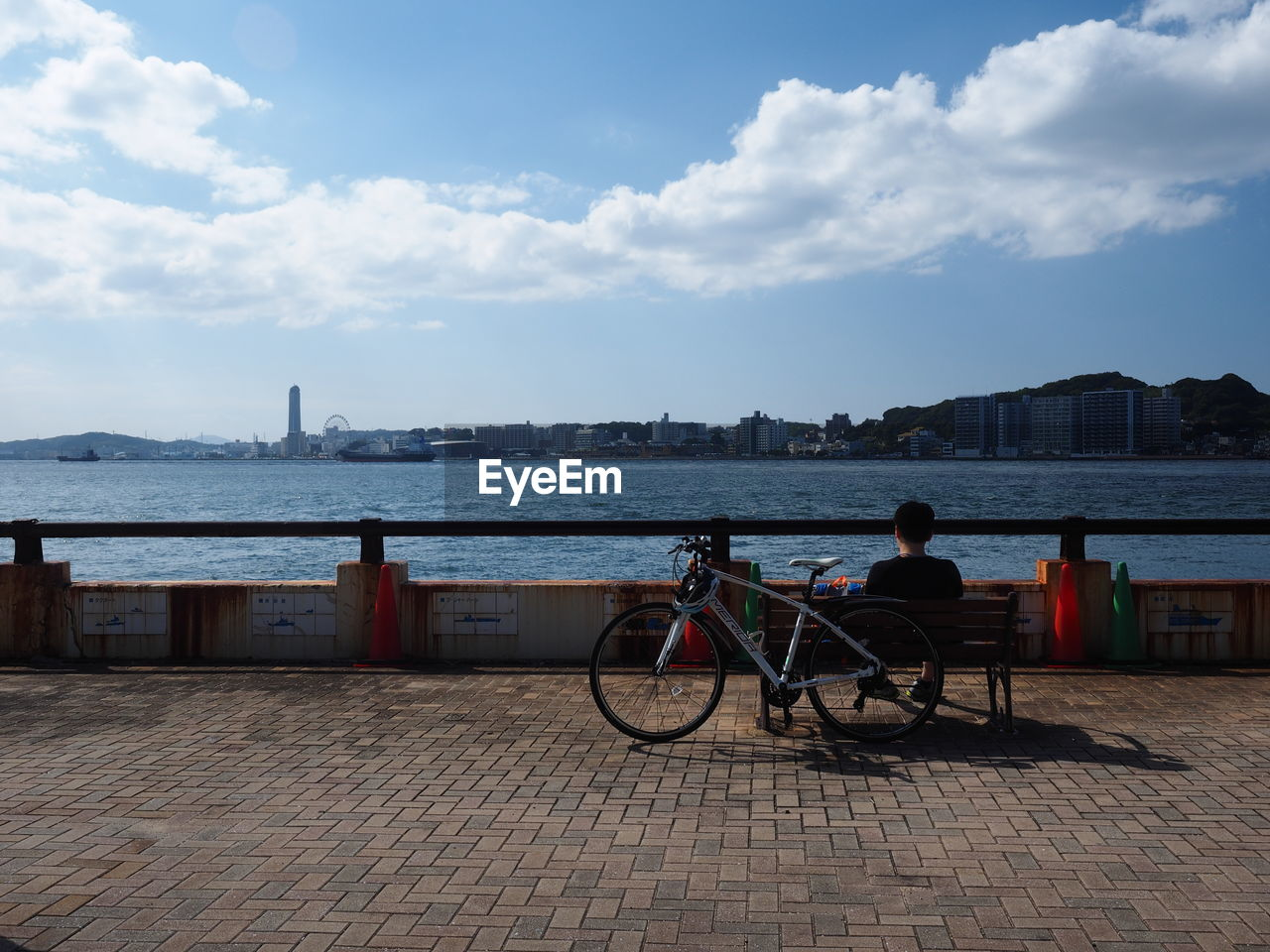 sky, bicycle, cloud - sky, architecture, transportation, water, mode of transportation, city, built structure, building exterior, nature, real people, land vehicle, people, nautical vessel, lifestyles, day, sea, outdoors