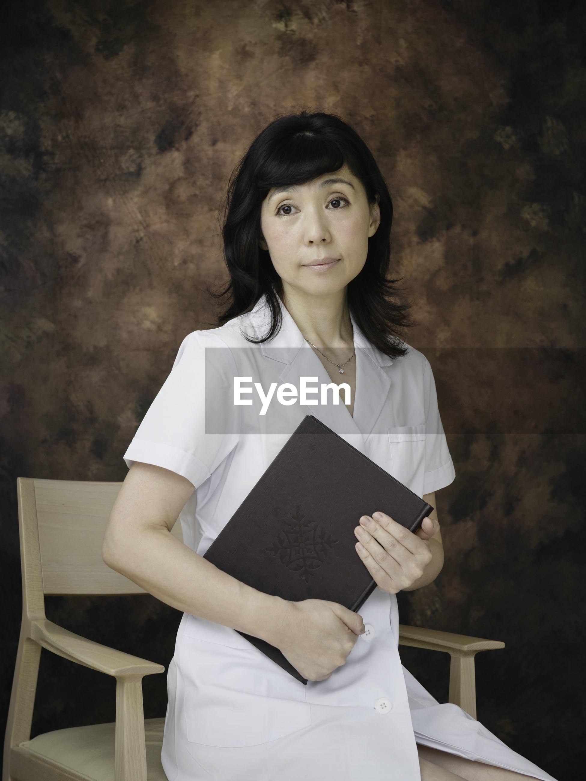Portrait of nurse sitting on chair against wall