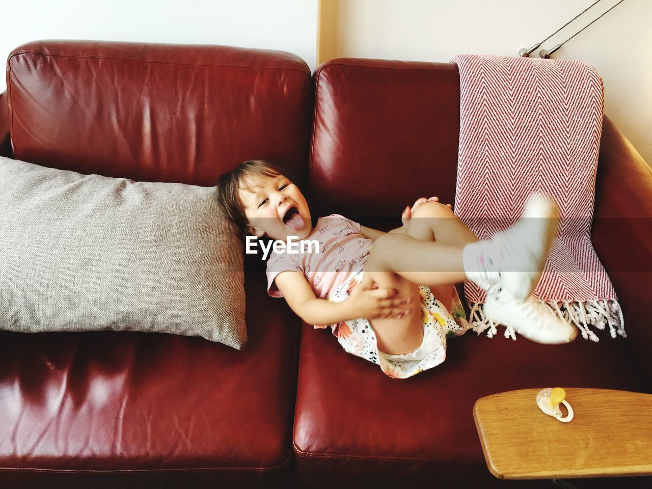 indoors, one person, relaxation, furniture, sofa, lifestyles, lying down, child, childhood, women, real people, front view, young adult, home interior, leisure activity, innocence, females, resting