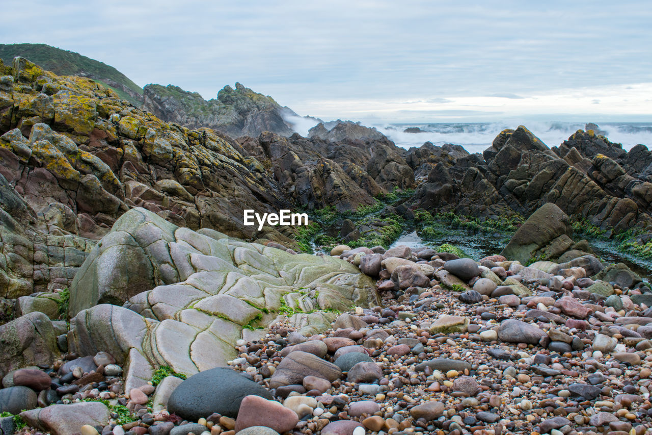 rock - object, nature, pebble, beauty in nature, no people, day, outdoors, tranquil scene, sea, beach, pebble beach, tranquility, scenics, physical geography, sky, water
