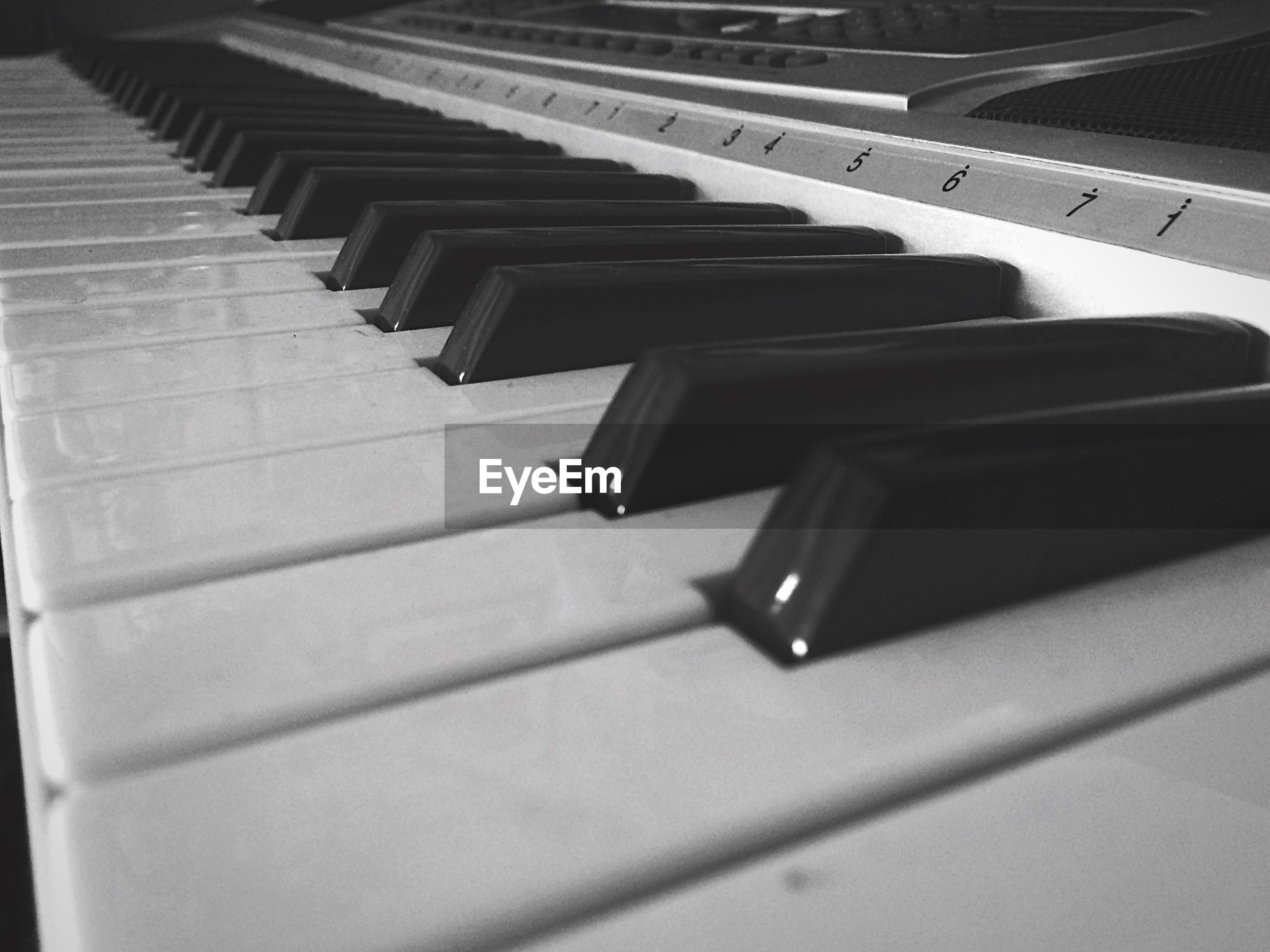 music, indoors, high angle view, arts culture and entertainment, musical instrument, piano key, musical equipment, close-up, piano, in a row, shadow, no people, technology, still life, part of, black color, repetition, pattern, guitar, white color