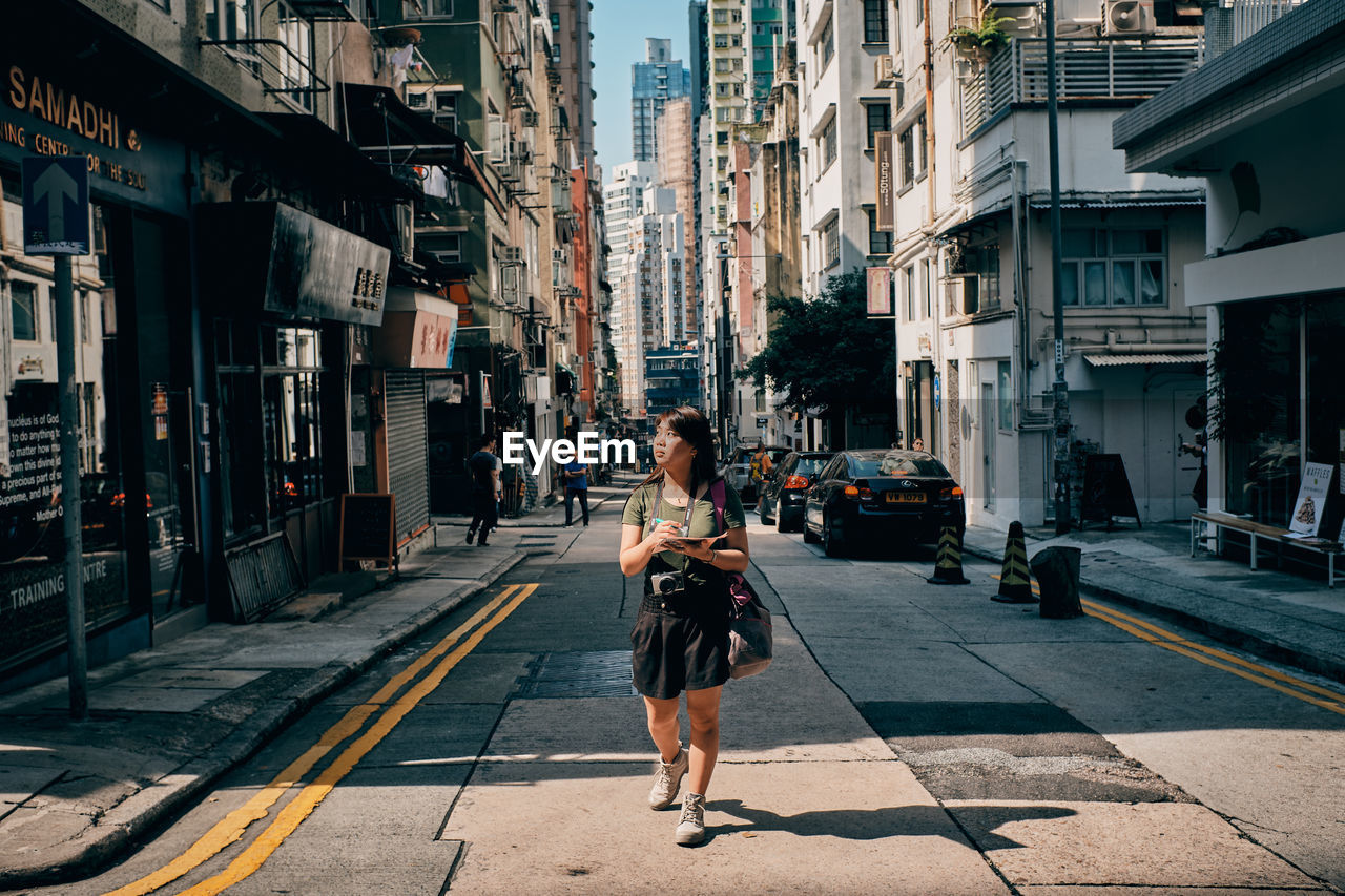 FULL LENGTH OF WOMAN ON STREET AMIDST BUILDINGS