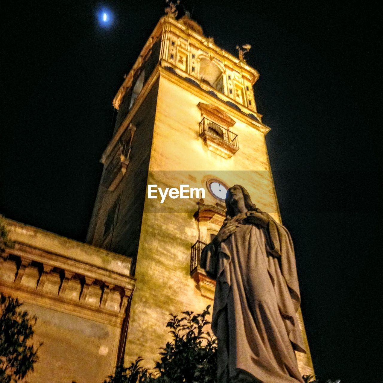 statue, low angle view, night, architecture, religion, built structure, male likeness, human representation, sculpture, spirituality, travel destinations, illuminated, building exterior, outdoors, sky, no people