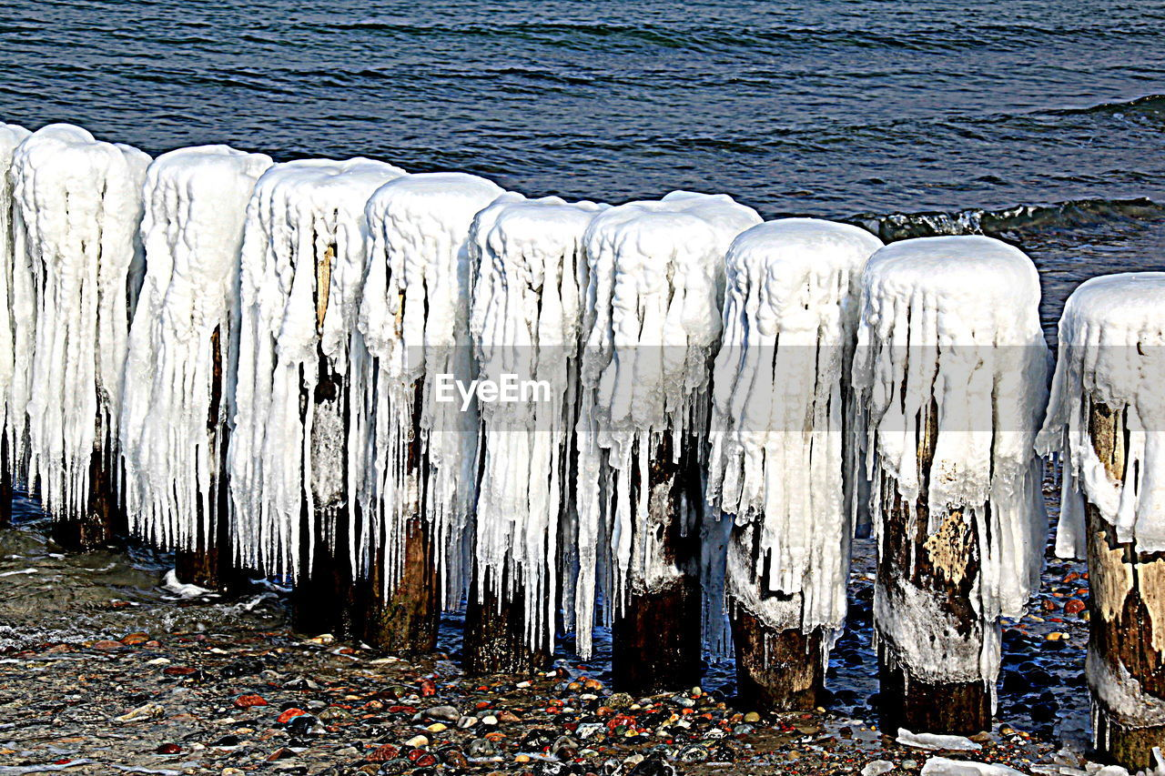 no people, day, cold temperature, nature, winter, ice, environment, frozen, wood - material, snow, outdoors, large group of objects, land, water, in a row, beach, white color, environmental issues, non-urban scene, icicle