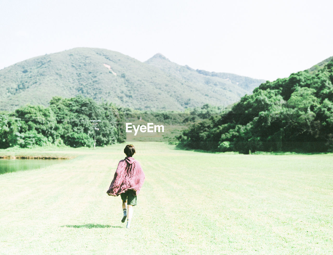 Rear view of woman running on field against mountain