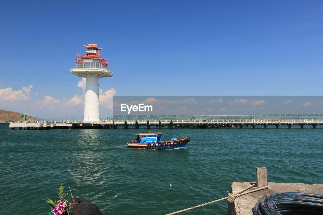sky, water, transportation, nautical vessel, built structure, mode of transportation, architecture, nature, sea, day, travel, building exterior, travel destinations, tourism, outdoors, incidental people, beauty in nature, lighthouse, waterfront