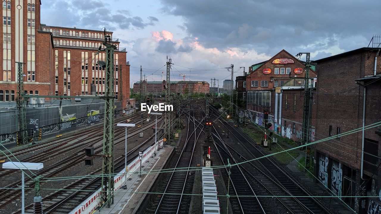 architecture, built structure, cloud - sky, sky, rail transportation, building exterior, transportation, track, railroad track, high angle view, mode of transportation, nature, train, city, building, public transportation, outdoors, train - vehicle, street, shunting yard