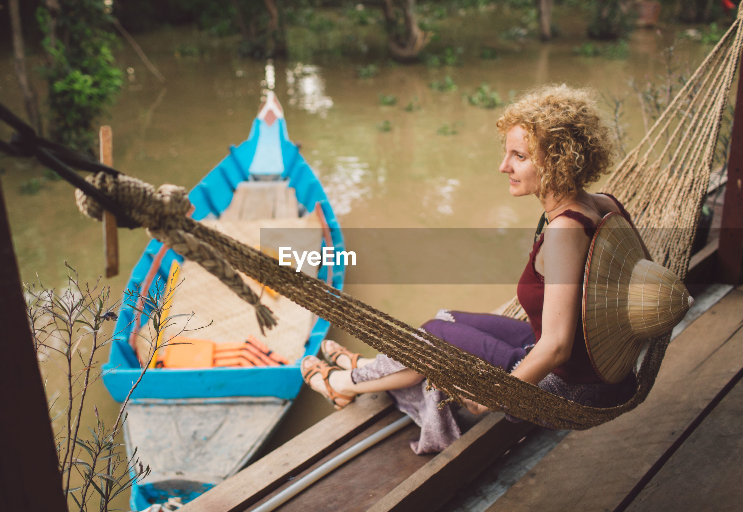 Side view of mid adult woman looking away while sitting on hammock over lake