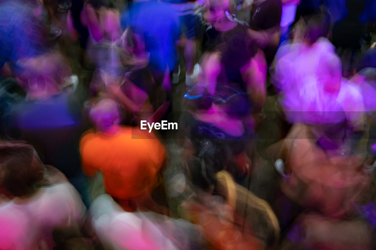 group of people, crowd, women, large group of people, motion, real people, blurred motion, dancing, enjoyment, adult, men, togetherness, lifestyles, leisure activity, celebration, indoors, multi colored, selective focus, night, purple, nightlife, excitement