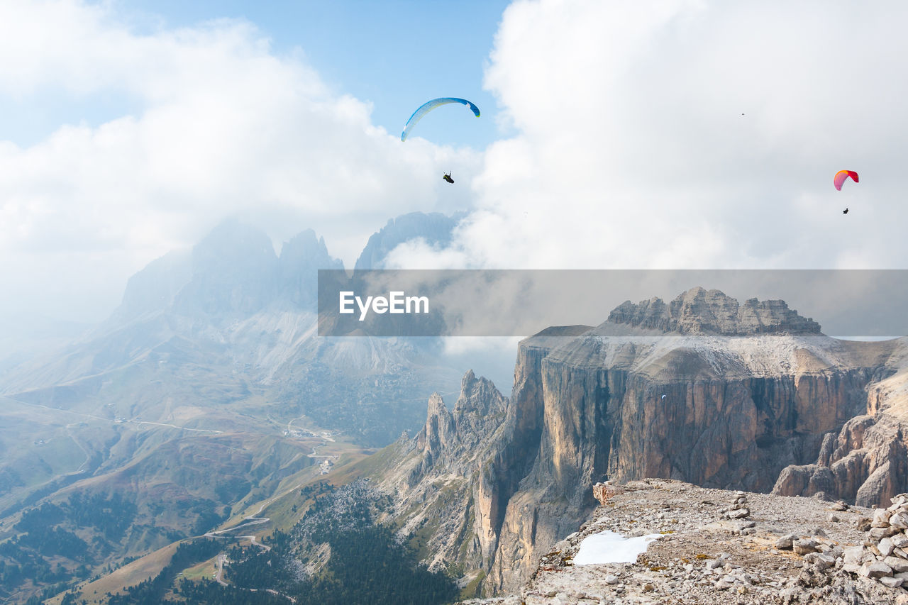 adventure, mountain, parachute, extreme sports, paragliding, mid-air, sky, beauty in nature, sport, flying, scenics - nature, mountain range, cloud - sky, day, nature, leisure activity, non-urban scene, unrecognizable person, transportation, gliding, freedom, outdoors