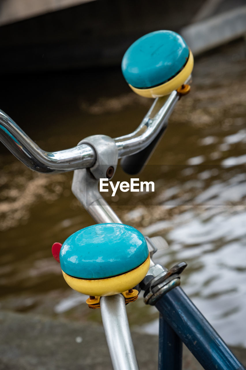 focus on foreground, metal, water, close-up, day, bicycle, no people, transportation, handlebar, lock, mode of transportation, outdoors, multi colored, blue, land vehicle, nature, architecture, high angle view, motion, turquoise colored, flowing