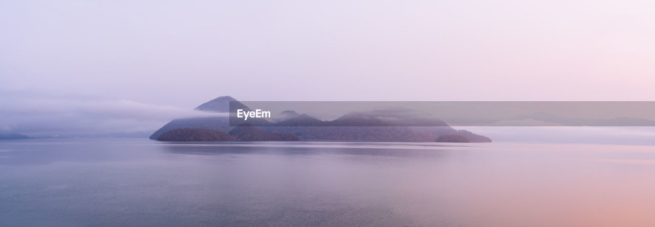 water, sky, tranquil scene, beauty in nature, tranquility, scenics - nature, waterfront, sea, no people, idyllic, nature, fog, non-urban scene, cloud - sky, outdoors, copy space, rock, headland