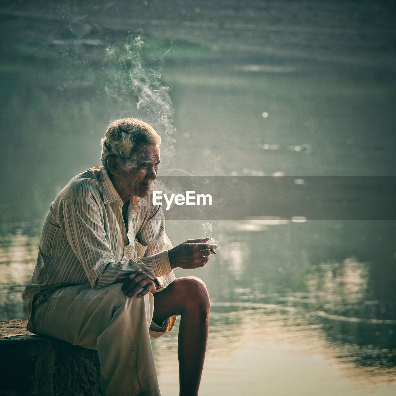 Thoughtful senior man smoking by lake