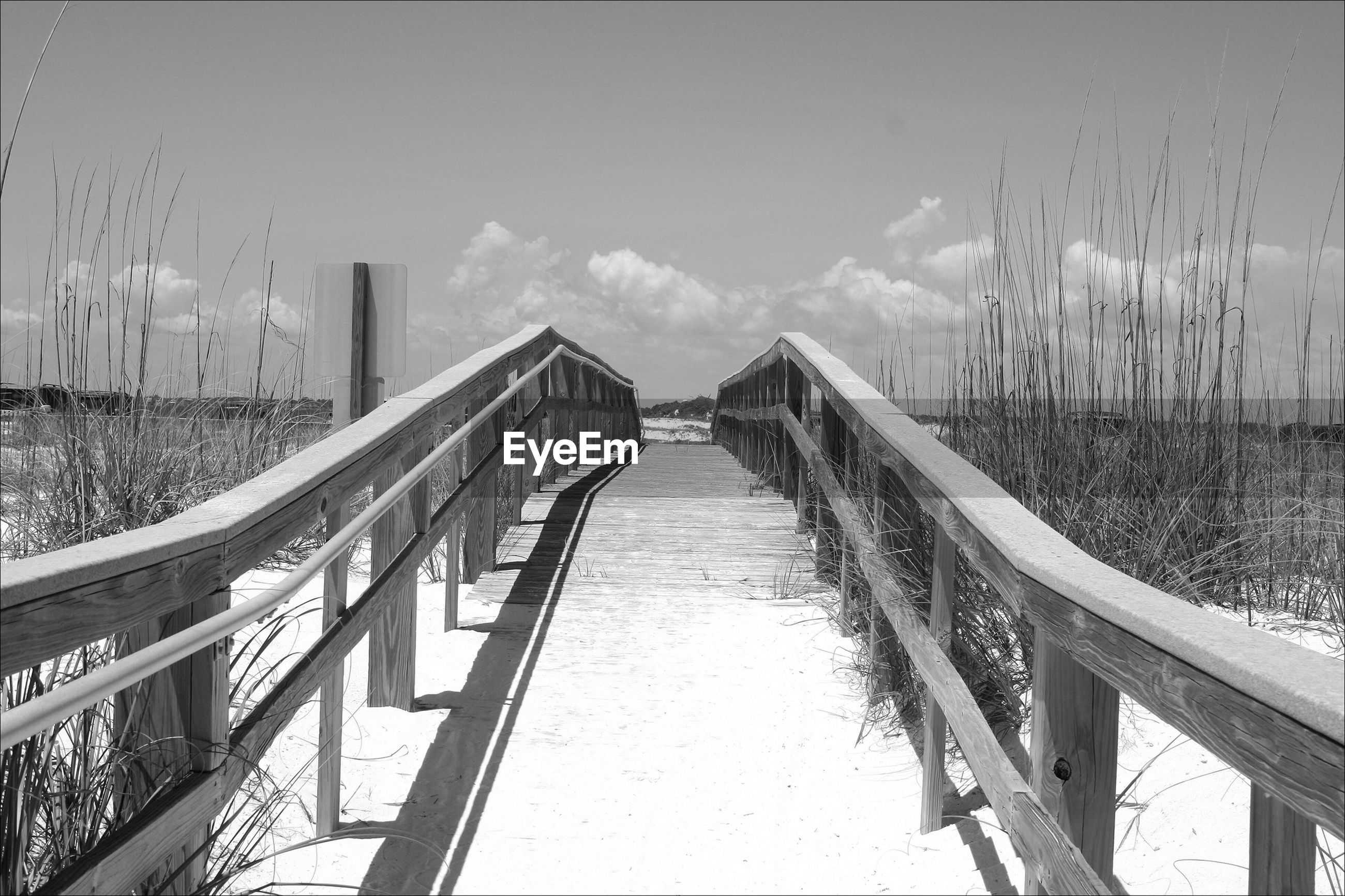 Boardwalk over river on sunny day
