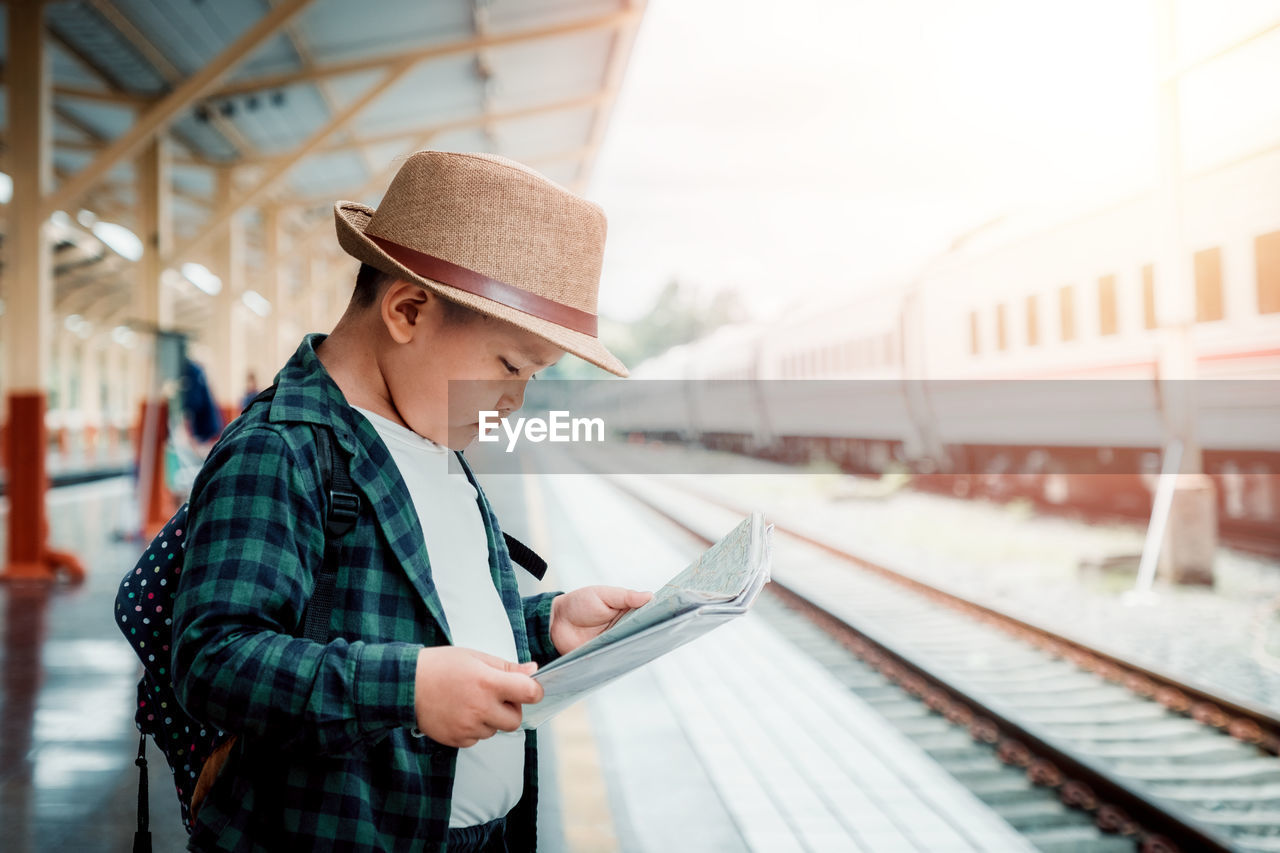 rail transportation, hat, clothing, track, real people, railroad track, one person, public transportation, standing, lifestyles, focus on foreground, train - vehicle, train, transportation, looking, young adult, railroad station platform, railroad station, mode of transportation, outdoors