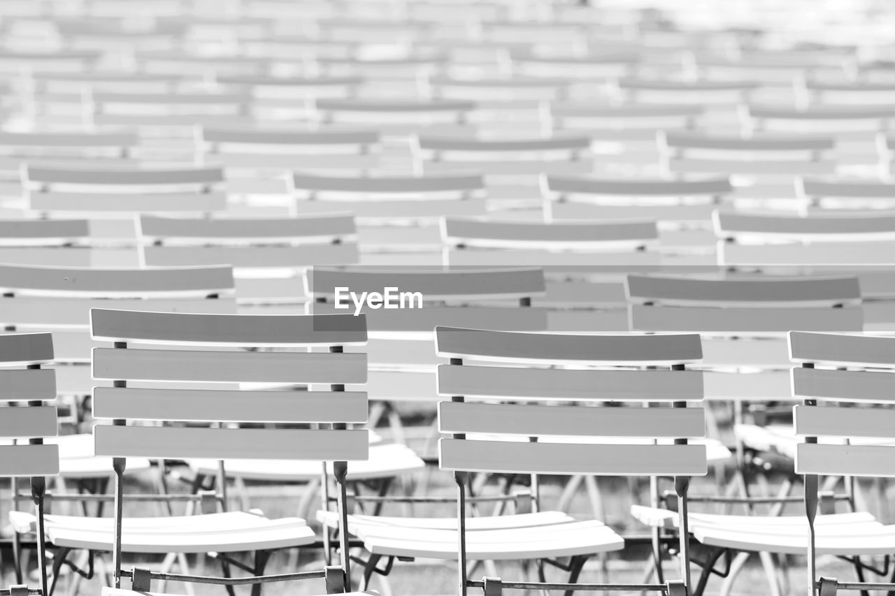 seat, in a row, chair, empty, table, absence, focus on foreground, group of people, large group of objects, repetition, auditorium, seminar, arrangement, education, white color, indoors, learning, people, spectator