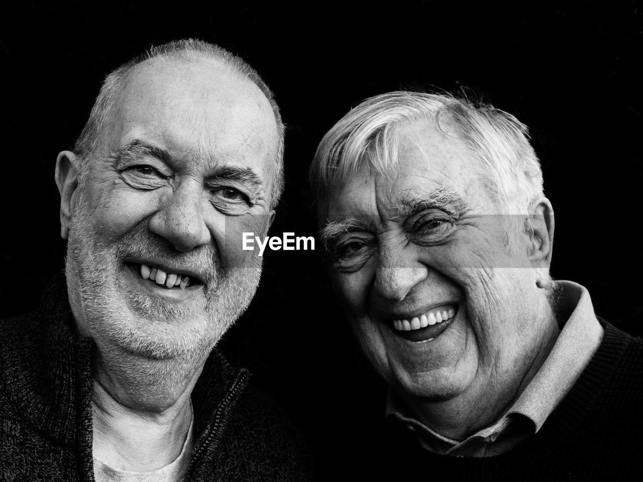 Portrait Of Smiling Senior Men Against Black Background