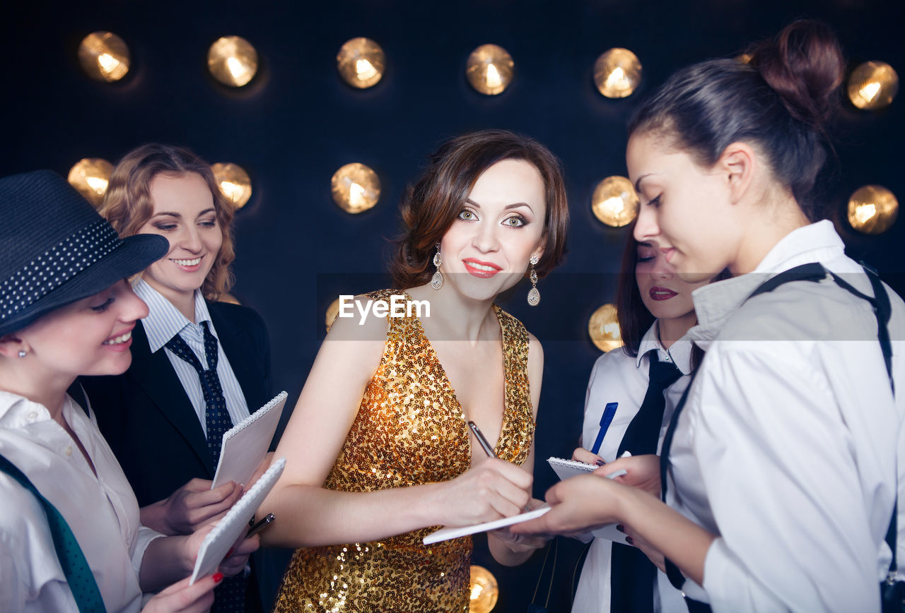 Female celebrity signing autograph for fans