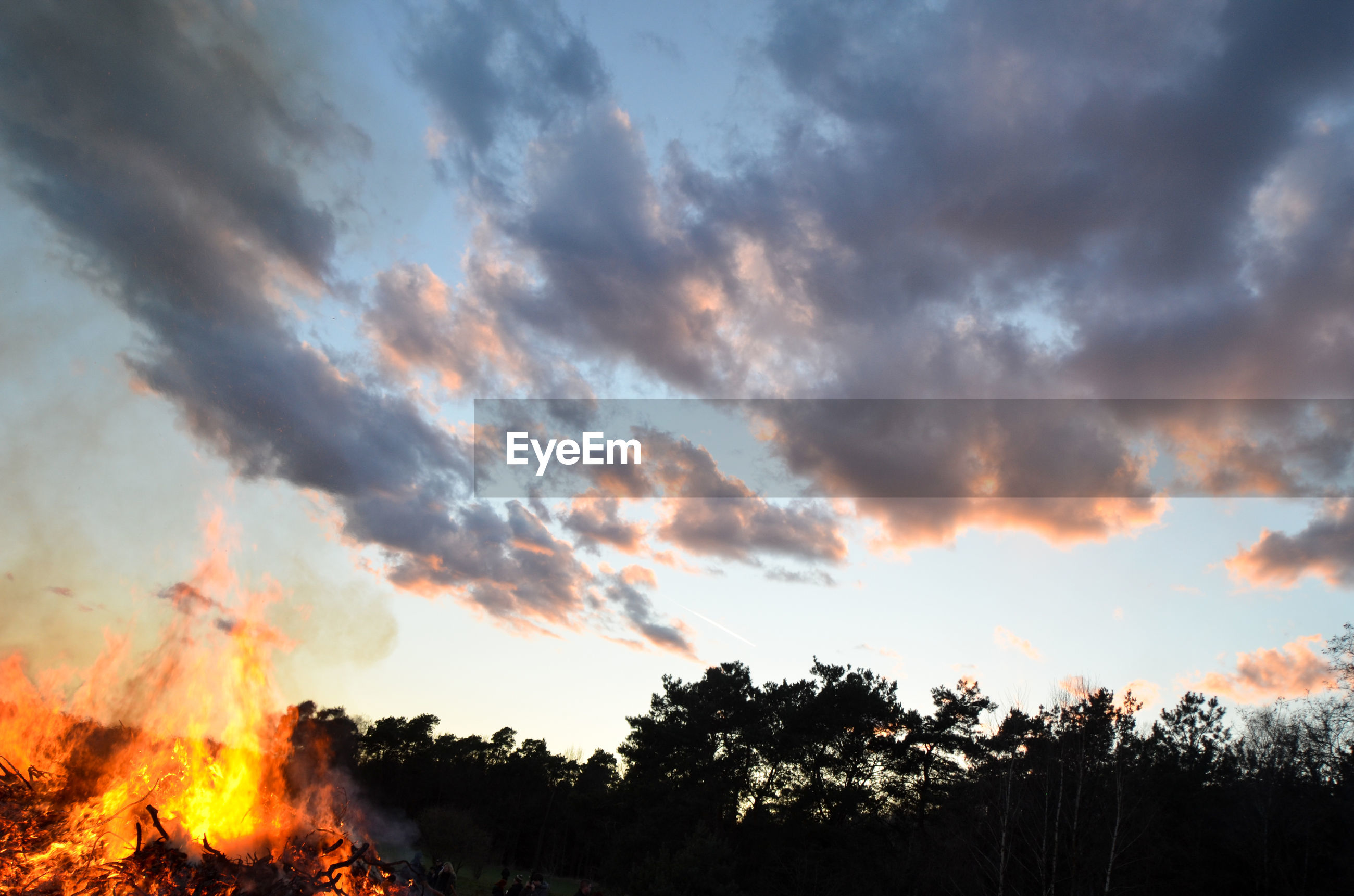 Low angle view of bonfire by silhouette trees against sunset sky during easter