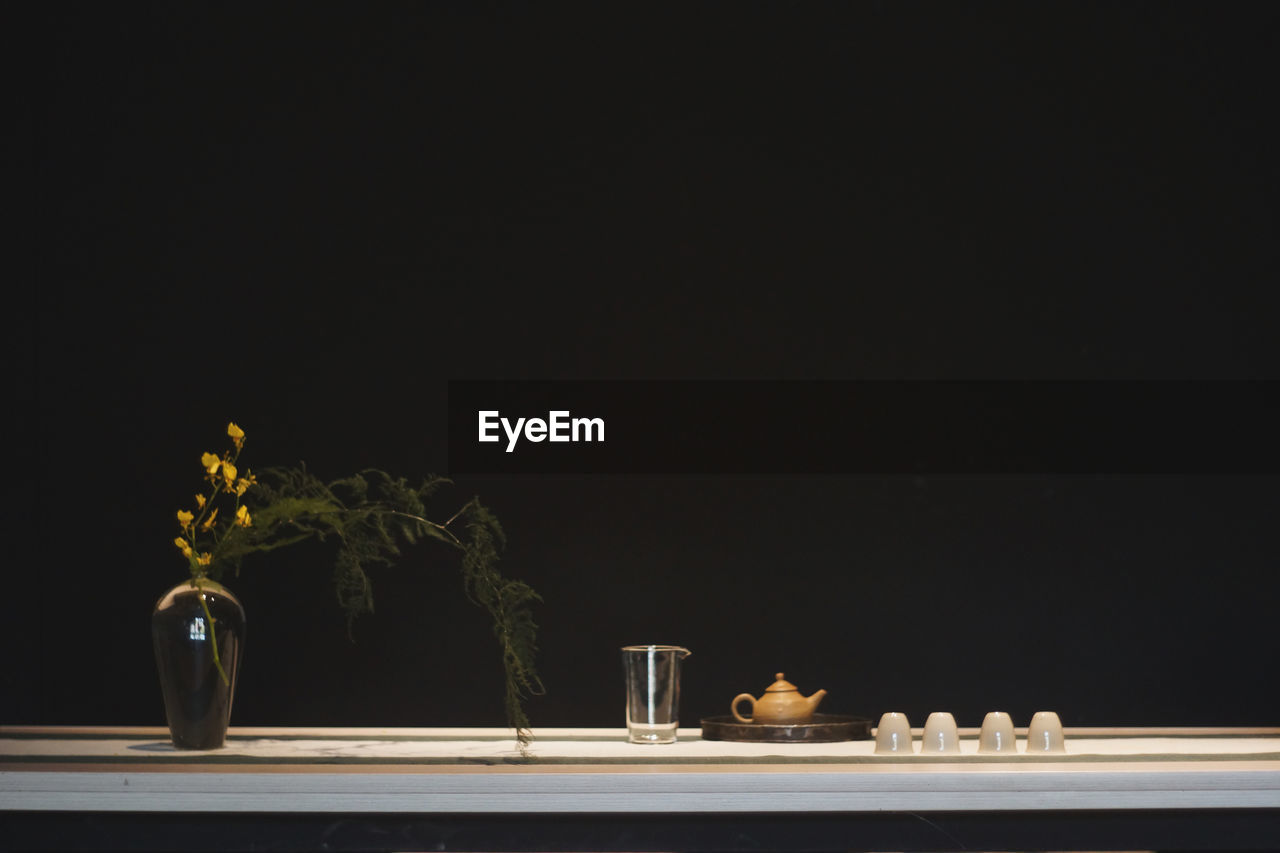 Close-up of vase and crockery on table against black background