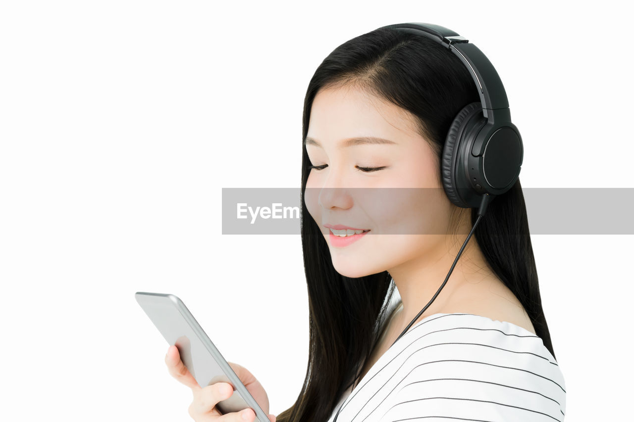 Smiling Young Woman Listening Music On Headphones Against White Background