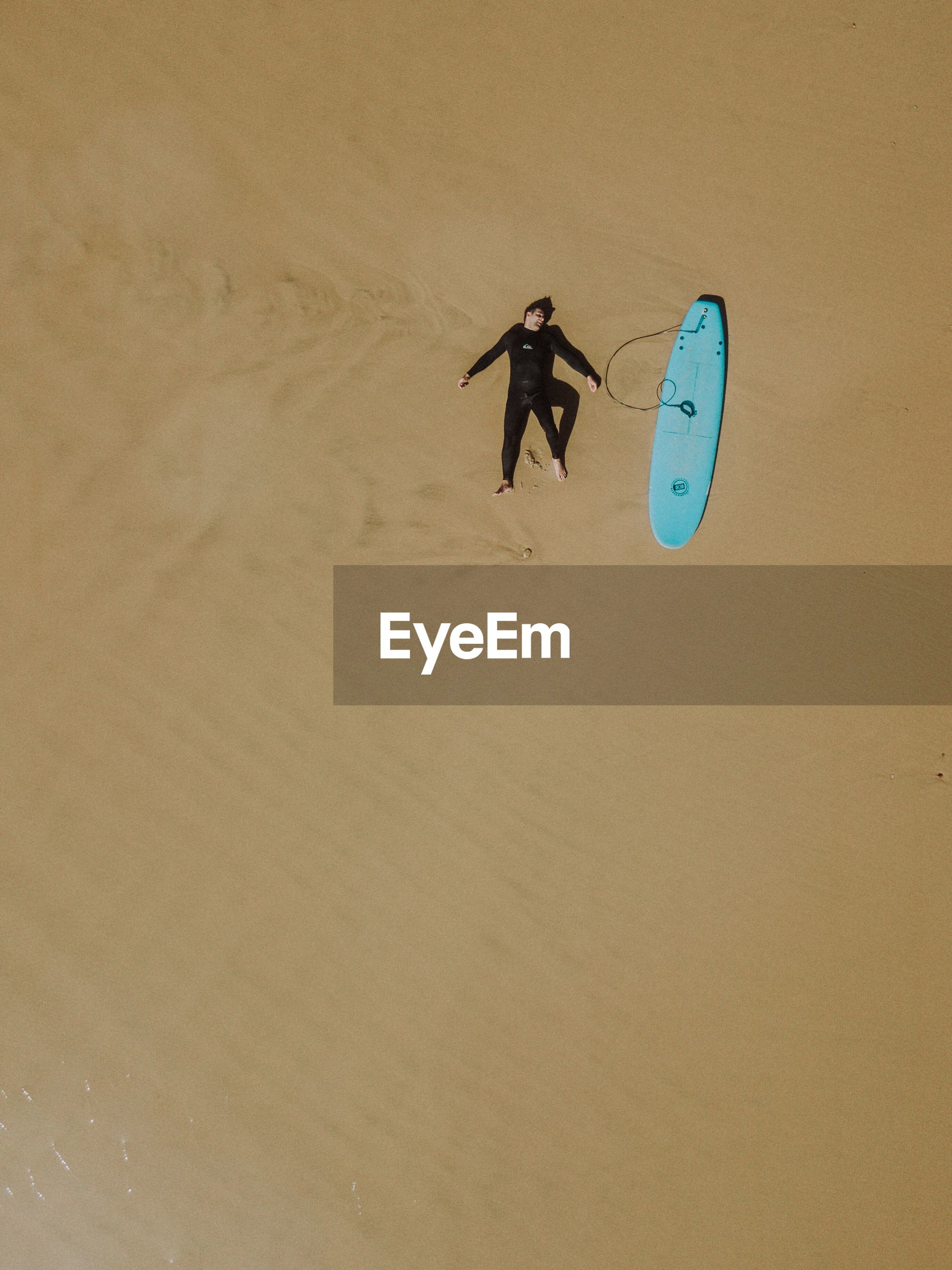 Drone view of surfer lying on sand at beach